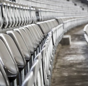 some rows of gray stadium seats, shoot from the side